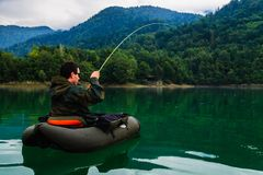 Fisherman fighting with big trout, Slovenia. Fisherman fighting with big trout while floating with bellyboat on lake in Jesenice, Slovenia. Cloudy day after rain Royalty Free Stock Images