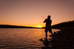 Fisherman Fighting a Fish at Sunset Royalty Free Stock Photo