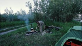 A fisherman by the fire. The distant plan of a fisherman raking coal in a fire stock video