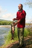 Fisherman with the fish. The fisherman with the fish on the river bank, Kamchatka Royalty Free Stock Images