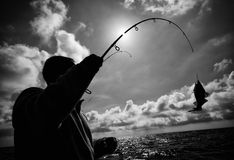Fisherman and fish hooked Royalty Free Stock Photo