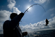 Fisherman and fish hooked Royalty Free Stock Photography