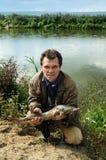 Fisherman with Fish Siberian Stargeon Stock Photo