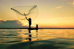 Fisherman. Fisher are sown dry river at sunset Royalty Free Stock Image