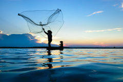 Fisherman. Fisher are sown dry river at sunset Stock Photos