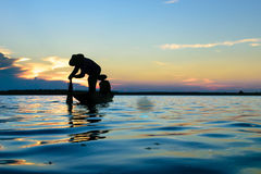 Fisherman. Fisher are sown dry river at sunset Royalty Free Stock Photography