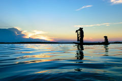 Fisherman. Fisher are sown dry river at sunset Royalty Free Stock Images
