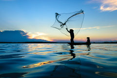 Fisherman. Fisher are sown dry river at sunset Stock Photo