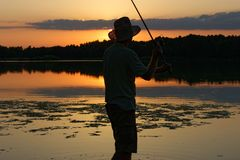Fisherman. Catching the fish during sunset Royalty Free Stock Photo