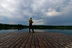 Fisherman. Catching the fish from wooden pier during cloudy day Stock Images