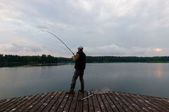 Fisherman. Catching the fish from wooden pier during cloudy day Royalty Free Stock Images