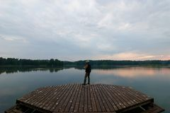 Fisherman. Catching the fish from wooden pier during cloudy day Stock Photography