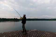 Fisherman. Catching the fish from wooden pier during cloudy day Royalty Free Stock Image