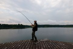 Fisherman. Catching the fish from wooden pier during cloudy day Stock Photos