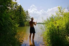 Fisherman. In the lake during sunny day Stock Images
