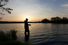 Fisherman. At the lake during sunset Royalty Free Stock Images