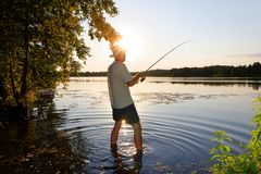 Fisherman. In the rays of the setting sun Royalty Free Stock Image