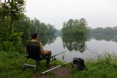 Fisherman. Sitting on the chair and fishing during cloudy day Stock Photo
