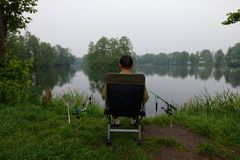 Fisherman. Sitting on the chair and fishing during cloudy day Royalty Free Stock Image