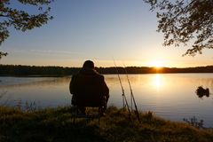 Fisherman. Sitting on the chair and fishing on the shore of lake during sunrise Royalty Free Stock Images