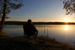 Fisherman. Sitting on the chair and fishing on the shore of lake during sunrise Stock Photo