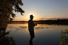 Fisherman. Standing in the lake and catching the fish stock photography