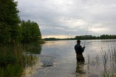 Fisherman. Standing in the lake and catching the fish on cloudy day stock images
