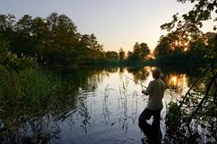 Fisherman. Standing in the lake and catching the fish during sunset Royalty Free Stock Image