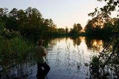 Fisherman. Standing in the lake and catching the fish during sunset Stock Photo