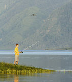 The fisherman fishes on bank of beautiful lake Stock Images
