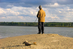 Fisherman fishes on a shallow Stock Images