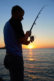 Fisherman fishes at the  sunset Stock Photo