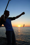 Fisherman fishes at the  sunset Royalty Free Stock Photos