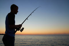 Fisherman fishes at the  sunset Royalty Free Stock Image