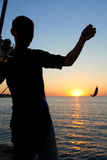 Fisherman fishes at the  sunset Royalty Free Stock Photography