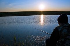 Fisherman fishing. Man sitting on the shore of a lake, fishing Royalty Free Stock Images