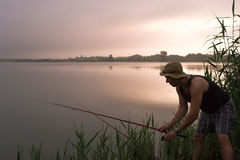 Fisherman fishing on the bank of the lake at sunrise. Fisher man fishing with rod on a lake at misty foggy sunrise in the summer Royalty Free Stock Photo