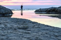 Fisherman fishing on the waterfront and admiring the sunset. royalty free stock photography