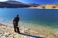 Fisherman fishing on blue lake. Fisherman fishing on beautiful blue lake Royalty Free Stock Image