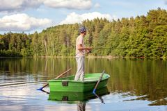 A fisherman in a boat. A fisherman is fishing in a boat on a beautiful lake Royalty Free Stock Images