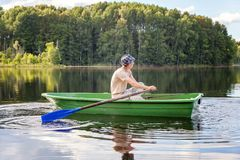 A fisherman in a boat. A fisherman is fishing in a boat on a beautiful lake Royalty Free Stock Image