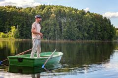 A fisherman in a boat. A fisherman is fishing in a boat on a beautiful lake Royalty Free Stock Photo