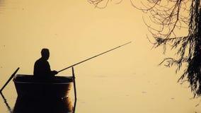 Fisherman fishing boat. Fisherman fishing from boat silhouette stock footage