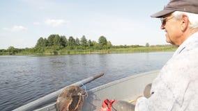 Fisherman fishing on boat stock video