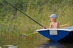 Fisherman is fishing from a boat Stock Image