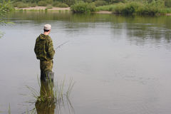 Fisherman fishing on calm river Stock Photos