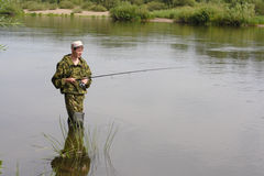 Fisherman fishing on calm river Royalty Free Stock Image