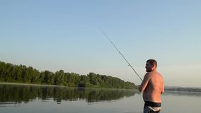 Fisherman fishing in a calm river in the morning. Man in fishing gear stending in a river and throws a fishing pole stock video footage