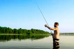 Fisherman fishing in a calm river in the morning. Man in fishing gear stending in a river and throws a fishing pole Royalty Free Stock Photography
