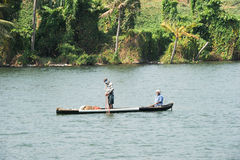 Fisherman fishing on a canoe near Kollam on Kerala backwaters Royalty Free Stock Images